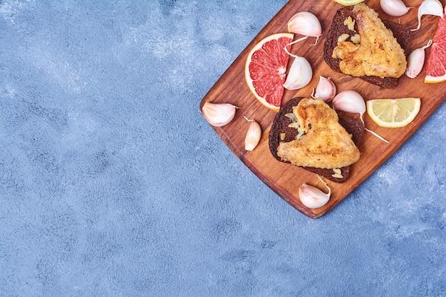 Ali di pollo fritte su una tavola di legno sull'azzurro Foto Gratuite