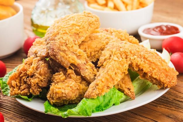 Alette di pollo fritte sulla tavola di legno. Foto Gratuite