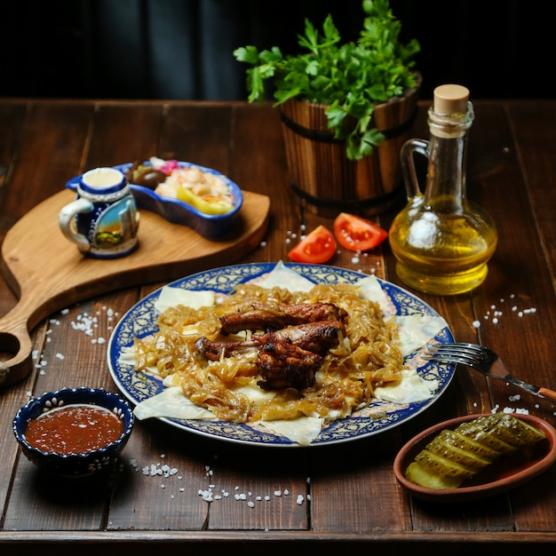 Fried chicken with onions on the table Free Photo