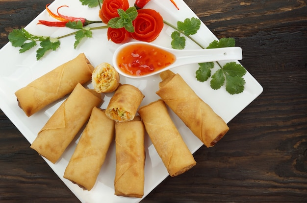 Fried chinese spring rolls served with chili sauce on wood Premium Photo