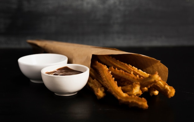 Fried churros with melted chocolate and sugar Free Photo