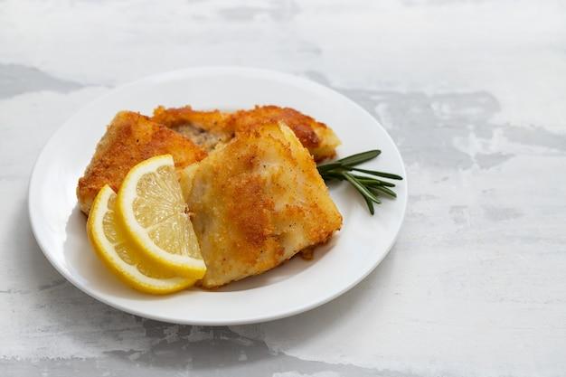 Жареная треска с лимоном на белой тарелке Premium Фотографии