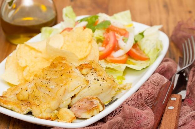 Жареная треска с картофелем и салатом на блюде Premium Фотографии