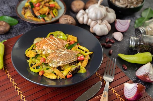 Жареный краб с порошком карри в тарелке со сладким перцем и помидорами. Бесплатные Фотографии