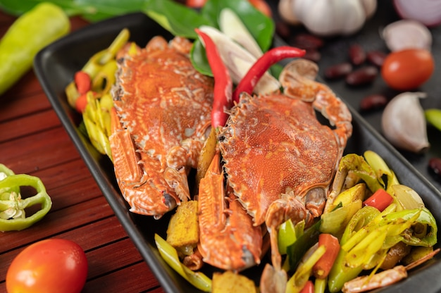 Granchio fritto con curry in polvere in un piatto con peperoni e pomodori. Foto Gratuite