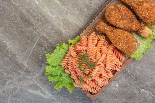 木の板に美味しいマカロニを添えたカリカリチキンナゲットの炒め物。 無料写真