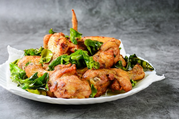 Fried crispy chicken wings with herbs Premium Photo