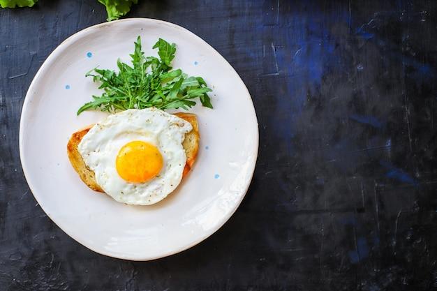 目玉焼きとトーストパンサラダおいしい朝食スナック卵黄とタンパク質部分の料理 Premium写真