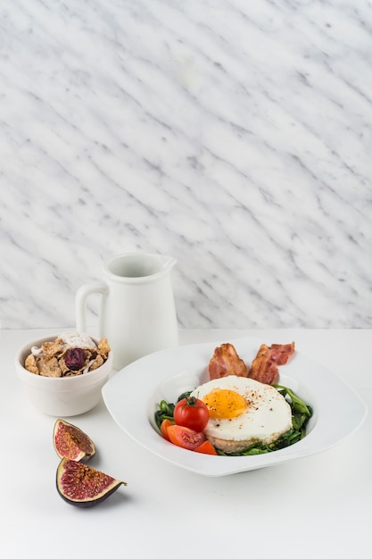 Fried egg; cornflakes and fig on white background against marble textured background Free Photo