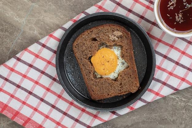 黒皿とお茶の黒パンスライスの中の目玉焼き。高品質の写真 無料写真