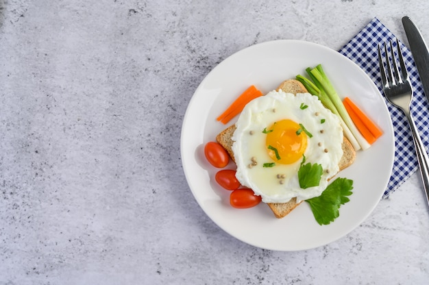 A fried egg laying on a toast, topped with pepper seeds with carrots and spring onions. Free Photo