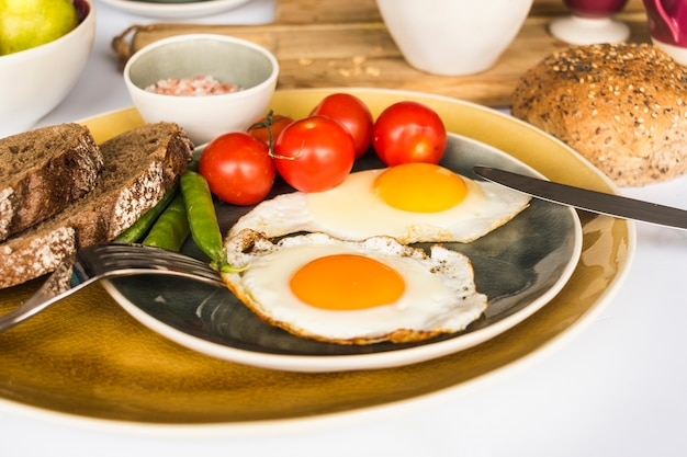 Fried egg omelette with bread, tomato and peas on plate Free Photo
