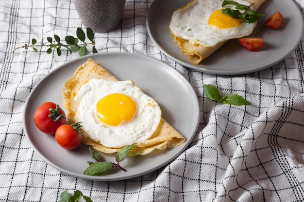 Fried egg with crepe and tomatoes Free Photo