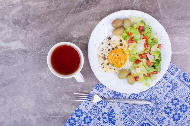 目玉焼きと野菜のサラダとお茶。 無料写真