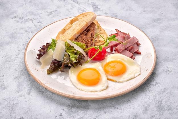 目玉焼き、トマト、ハム、チャバタのトースト、白い表面に目玉焼き。朝ごはん Premium写真