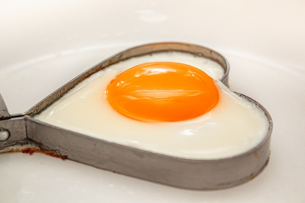 Fried eggs heart shape homemade meal on a frying pan. Premium Photo