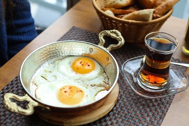 Uova fritte in padella sulla tavola di legno tè in pane armudy Foto Gratuite