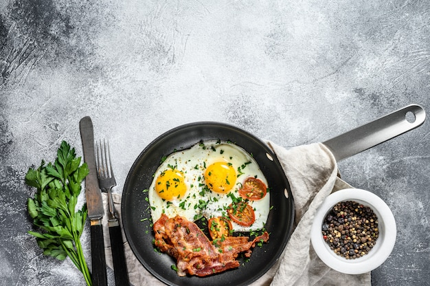 Fried eggs with bacon in a pan. keto diet. keto breakfast. low carb diet concept. high fat diet. gray background. top view. space for text Premium Photo