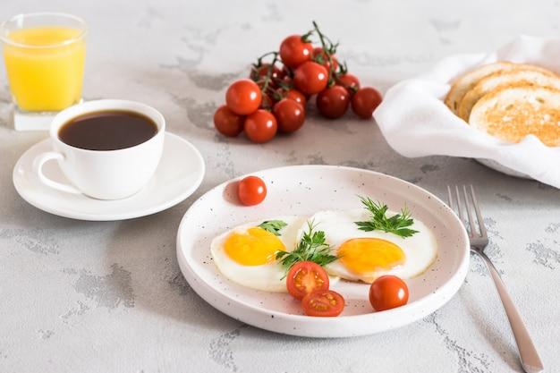 ハーブ、赤いトマト、トースト、コーヒー、フレッシュジュースと目玉焼き Premium写真