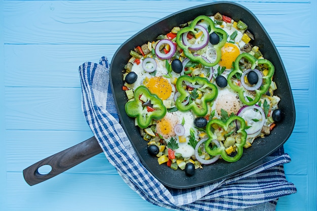 Fried eggs with vegetables in a pan. shakshuk. arabic cuisine proper nutrition. view from above. Premium Photo