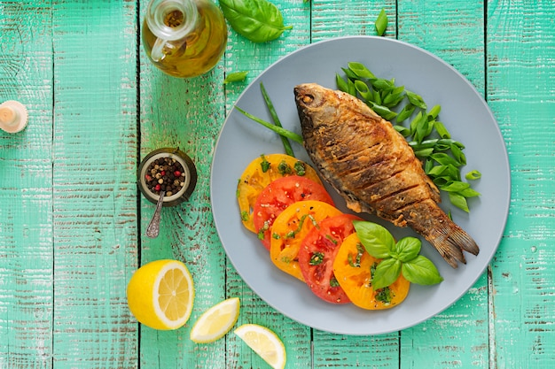 Fried fish carp and fresh vegetable salad on wooden table. flat lay. top view Free Photo