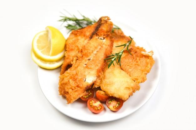 Жареное филе рыбы, нарезанное для стейка или салата, готовит еду со специями из трав, розмарина и филе лимона / тилапии, хрустящая рыба, подается на тарелке Premium Фотографии