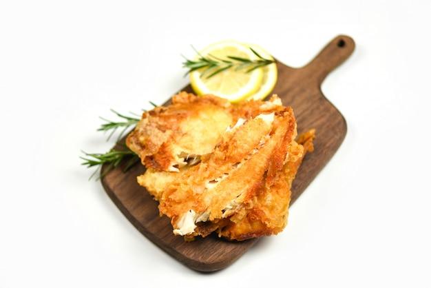 Жареное филе рыбы, нарезанное для стейка или салата, готовит еду с пряностями, специями, розмарином и лимоном, филе тилапии, рыба хрустящая, подается на деревянной разделочной доске и на белом фоне Premium Фотографии