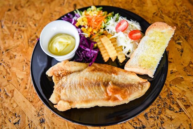Жареное рыбное филе - стейк из рыбы с соусом, картофелем фри, хлебом и свежими овощами на тарелке Premium Фотографии