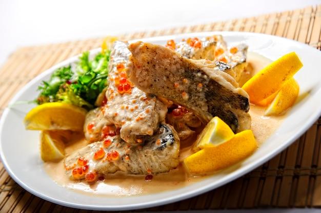 Жареное филе рыбы с картофелем фри на белом фоне. Premium Фотографии
