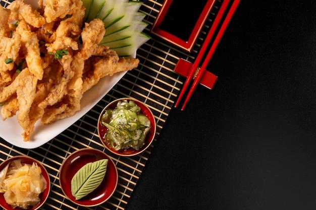 Жареные рыбные палочки на черном фоне Premium Фотографии