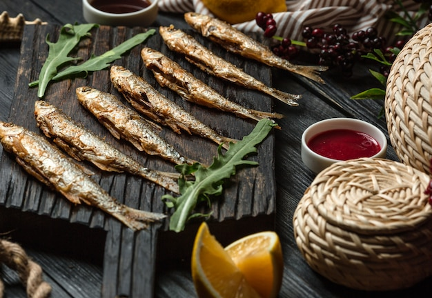 Fried fish set on wooden board Free Photo