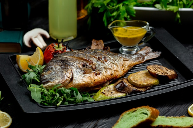 Fried fish with potatoes on furnace board Free Photo