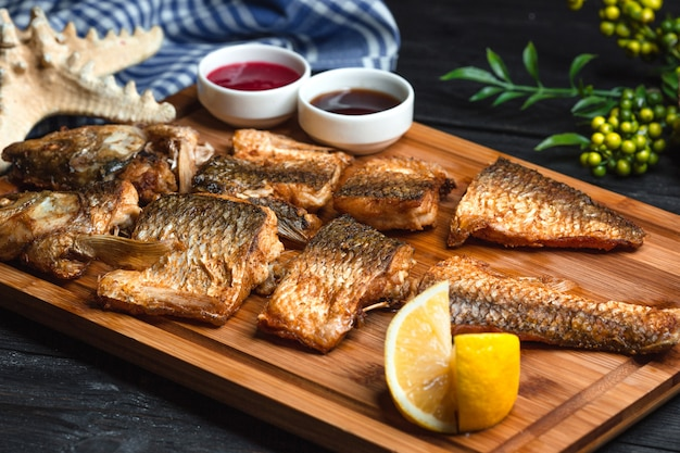 Fried fish with sauces on wooden board Free Photo