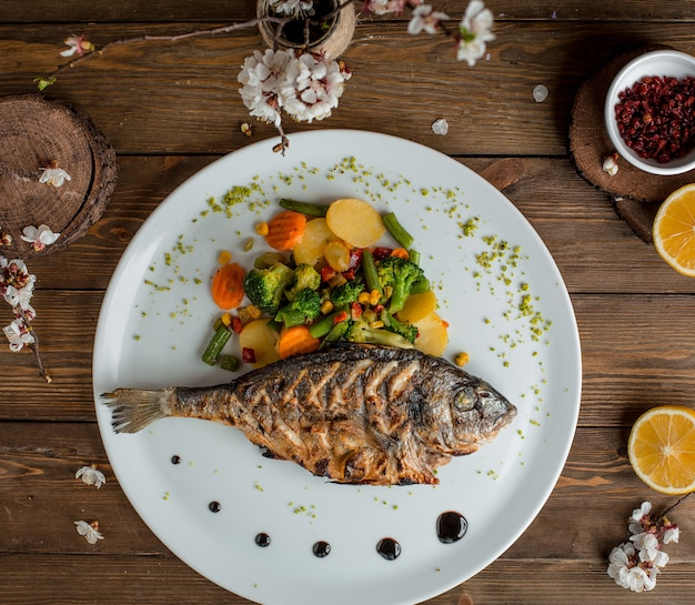 Fried fish with vegetables in the plate Free Photo