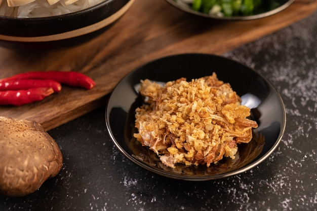 Aglio fritto sul piatto nero con peperoncino e shiitake. Foto Gratuite