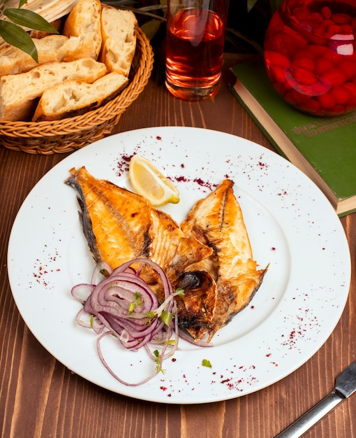 Fried, grilled fish served in white plate with onion salad, lemon and herbs Free Photo