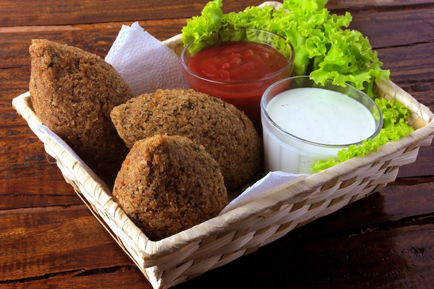 Fried kibbeh with tomato sauce in a basket Premium Photo