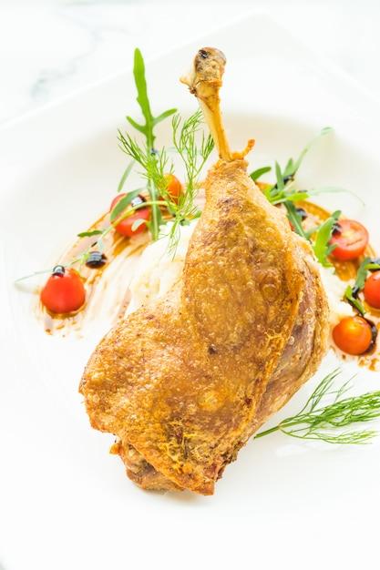 Fried leg duck with potato salad Free Photo
