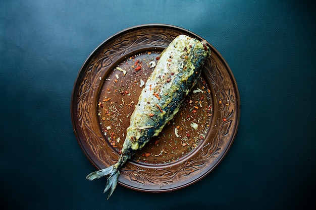 Fried mackerel on a plate, dark background. Premium Photo