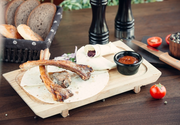 Fried meat kebab with lavash on wooden board Free Photo
