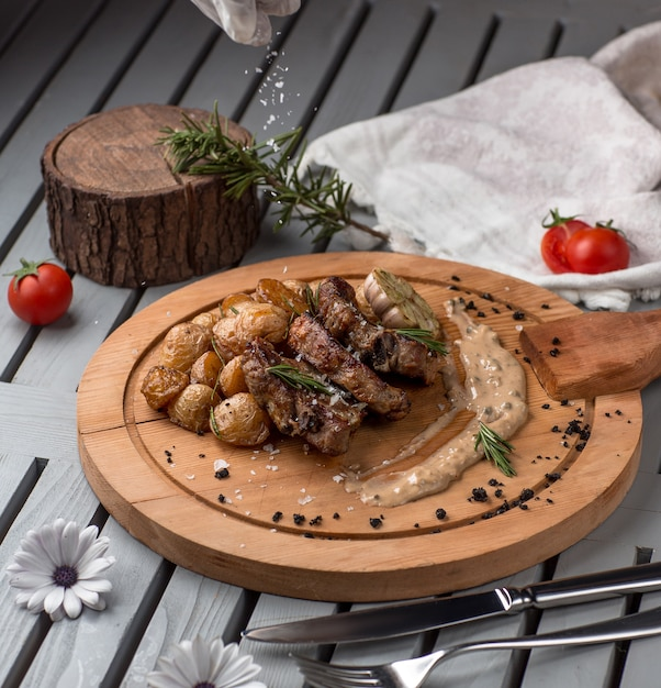 Fried meat and mushrooms on wooden board Free Photo