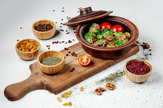 Жареное мясо с зеленью и помидорами в глиняном горшочке Бесплатные Фотографии