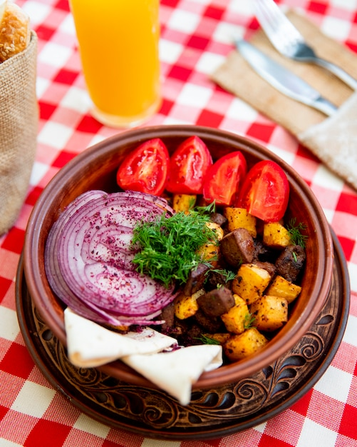 Fried meat with potatoes served with onions tomatoes and greens Free Photo