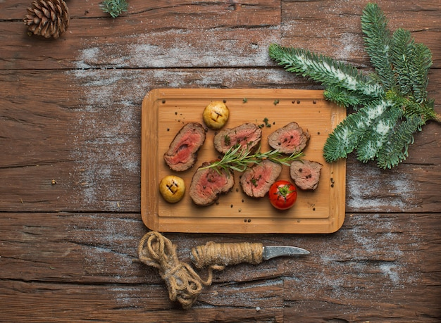 Fried meat with vegetables on wooden board Free Photo