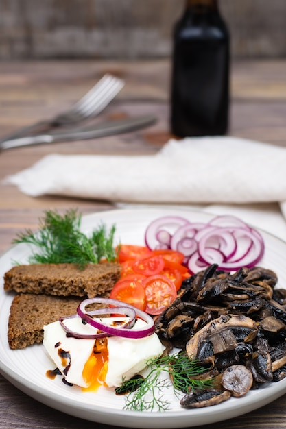 Fried mushrooms, poached egg, tomatoes, onions and dill on plate on wooden table Premium Photo