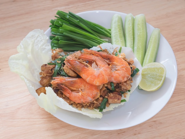 Fried noodle thai style with prawns and fresh vegetable called Free Photo