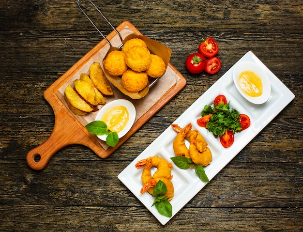 Fried nuggets and potatoes with sliced eggs and tomatoes Free Photo