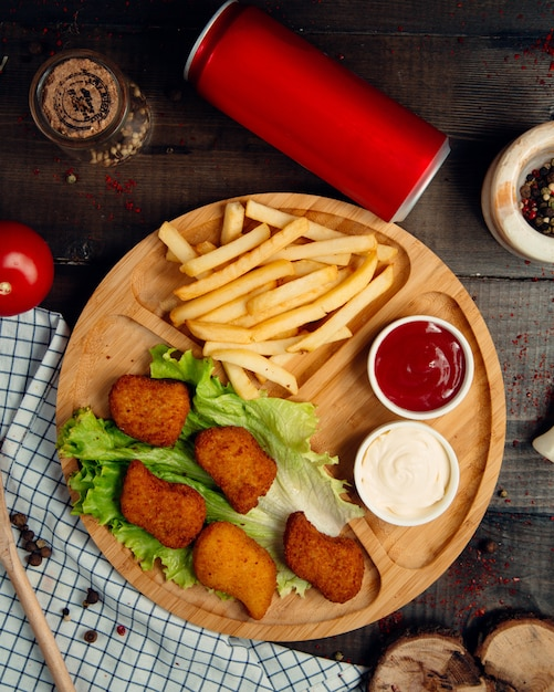 Fried nuggets with french fries on wooden board Free Photo