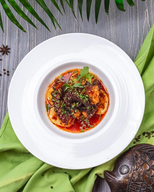 Жареный осьминог с овощами картофельная зелень томатная петрушка вид сверху Бесплатные Фотографии