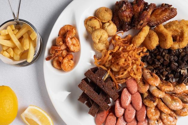 Жареные луковые кольца, панированные кальмары, хрустящий картофель, лимонные и жареные колбаски Premium Фотографии